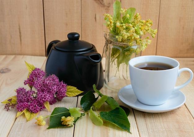 Lindebloemen en thee op een licht hout.