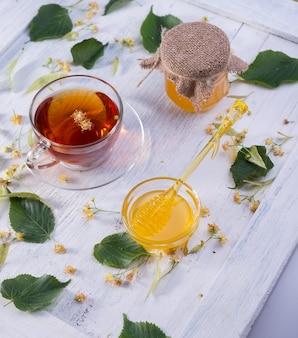 Lindehoning in pot en kom met een honingslepel