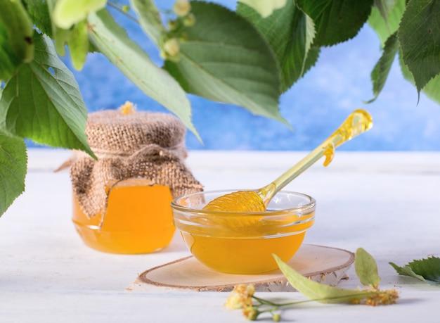 Linden honing in pot en kom met een honing beer op een witte houten tafel