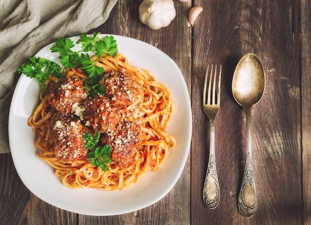 Linguine pasta met gehaktballen in tomatensaus en peterselie op rustieke houten achtergrond. bovenaanzicht.