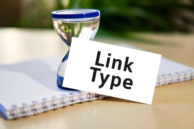 Link type zakelijke seo concept tekst op een witte notebook en zandloper klok, groene bladeren van bloemen