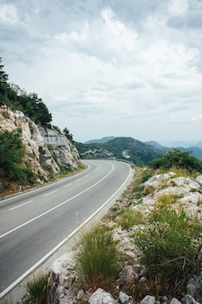 Linker bocht van bergweg met blauwe lucht en zee