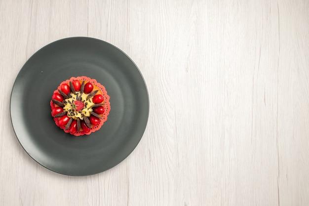 Linkerbovenaanzicht chocoladetaart afgerond met cornel en framboos in het midden in de grijze plaat op de witte houten achtergrond
