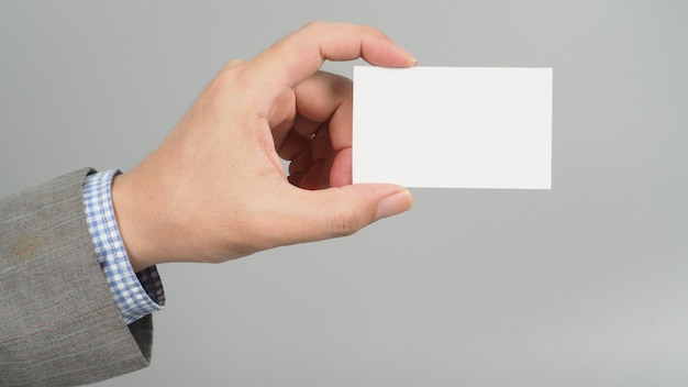 Linkerhand houdt een witte lege kaart vast en draagt een pak op een grijze achtergrond. zakenman concept