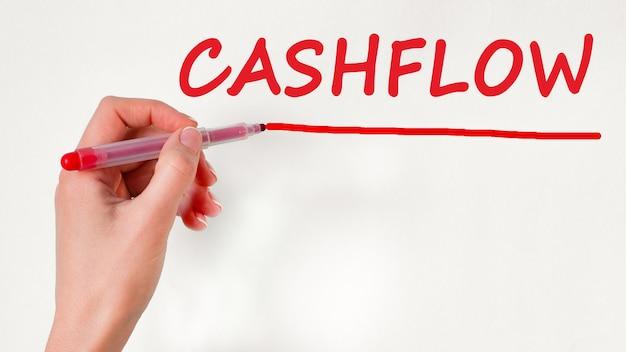 Linkerhand schrijven inscriptie cashflow met rode kleurmarkering, concept, stockafbeelding