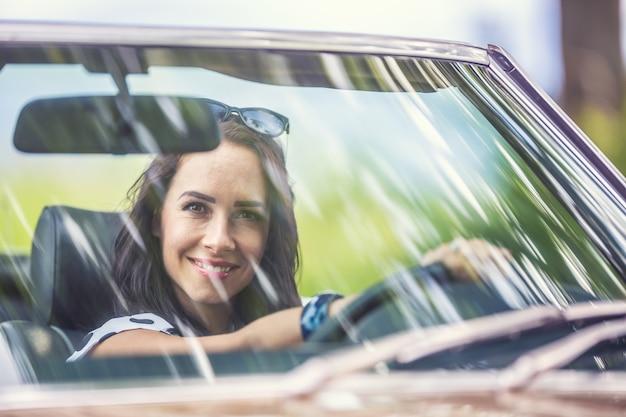 Links rijdende vrouw zit achter het stuur van een auto en glimlacht door de voorruit in de camera.