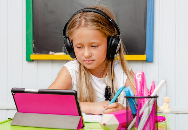 Linkshandig schattig schoolmeisje dat online bestudeert.