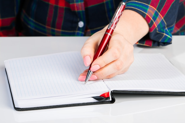 Linkshandige dag. zakenvrouw schrijft een notitie in notitieblok. het meisje houdt een pen in haar linkerclose-up.