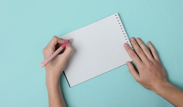 Linkshandige vrouw schrijft met een pen in een dagboek