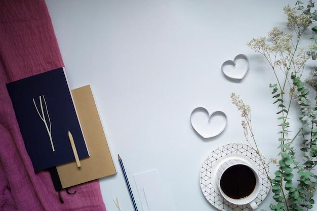Lintharten, notitieboekje en koffie op witte achtergrond, valentijnskaartendag.