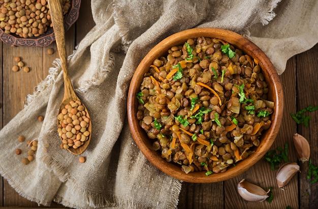 Linzen met wortel en ui in houten kom