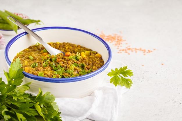 Linzenkerrie, indische keuken, tarka dal, witte achtergrond. veganistisch eten.