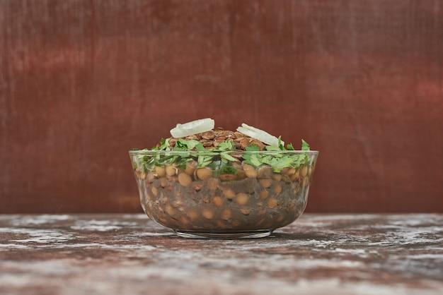 Linzensalade in een glazen beker met kruiden.