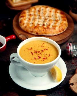 Linzensoep in een kom voor soepen en een schijfje citroen