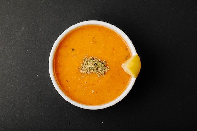 Linzensoep met kruiden en citroenplak.