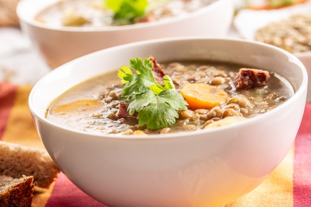 Linzensoep met stukjes gerookte varkensnek, wortel, aardappelen en koriander. traditioneel slowaaks, tsjechisch of oost-europees eten.