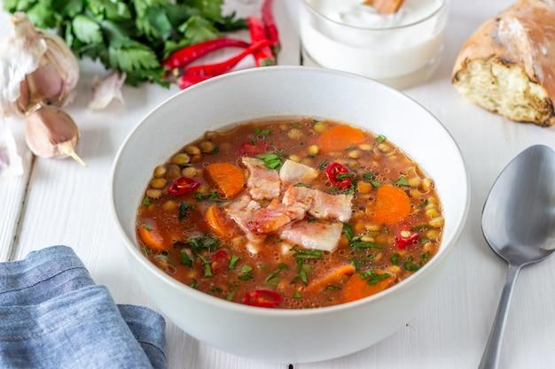 Linzensoep met wortelen en gebakken spek. recepten. duitse keuken. houten achtergrond.