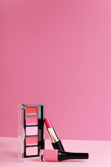 Lipgloss, blusher-palet, lippenstift op felroze achtergrond.