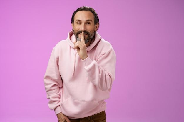 Lippen verzegeld geheim. portret verleidelijke brutale stijlvolle volwassen bebaarde man in roze hoodie vragen stil te houden toon shush shh gebaar wijsvinger ingedrukt mond lachend slinkse zelfvoldane gezicht, idee hebben.