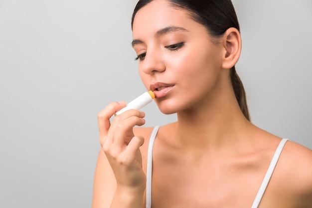 Lippenbescherming en verzorging. schoonheid vrouw balsem toe te passen op de lippen