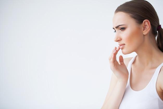 Lippenpijn, sluit omhoog portret van jong mooi peinzend meisje in witte sweater