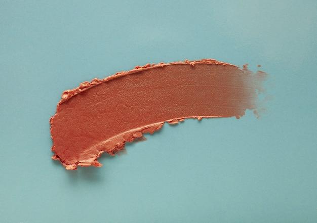 Lippenstift bruin veegmonster op blauwgrijs gekleurde achtergrond
