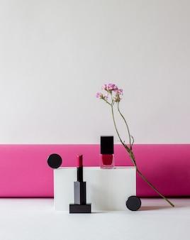 Lippenstift en nagellak met roze bloem. cosmetica. bedenken.