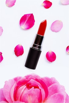 Lippenstift met rozenblaadjes op wit wordt geïsoleerd