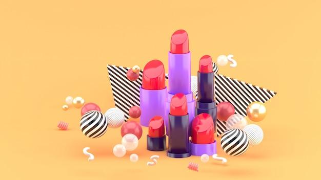 Lippenstift onder kleurrijke ballen op oranje. 3d-weergave.