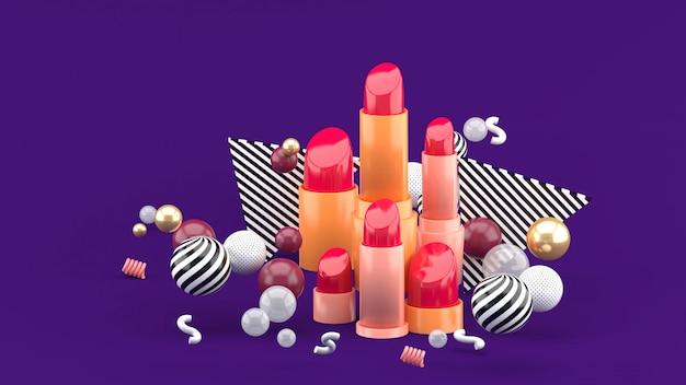 Lippenstift onder kleurrijke ballen op paars. 3d-weergave.