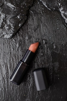 Lippenstift op de zwarte achtergrond van de leisteen