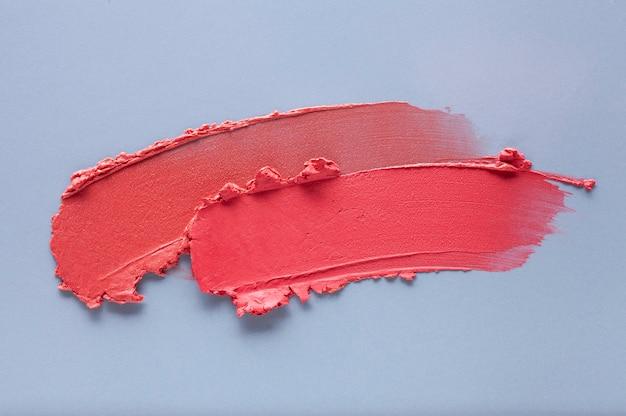 Lippenstift rood koraal veegmonster op blauwgrijs gekleurde achtergrond