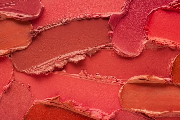 Lippenstift smudge swatch koraalrood oranje gekleurde achtergrond