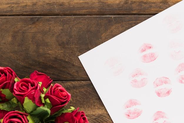Lippenstiftkussen op papier dichtbij mooie bloemen