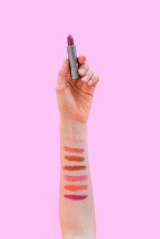 Lippenstiftstalen op de lippenstift van de vrouwenhandholding over roze achtergrond