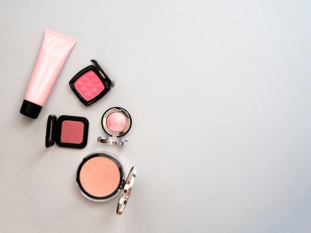 Lipstick, tools, eyeliner, blush, parfum, oogschaduw en poeder cosmetica in blauw thema make-up op frame voor promotie. set decoratieve cosmetica. ruimte kopiëren.