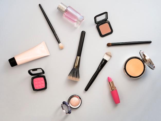 Lipstick, tools, eyeliner, blush, parfum, oogschaduw en poeder cosmetica in blauw thema make-up op frame voor promotie. set decoratieve cosmetica. uitverkooppakket