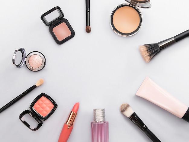 Lipstick, tools, eyeliner, blush, parfum, oogschaduw en poeder cosmetica in blauw thema make-up op frame voor promotie.