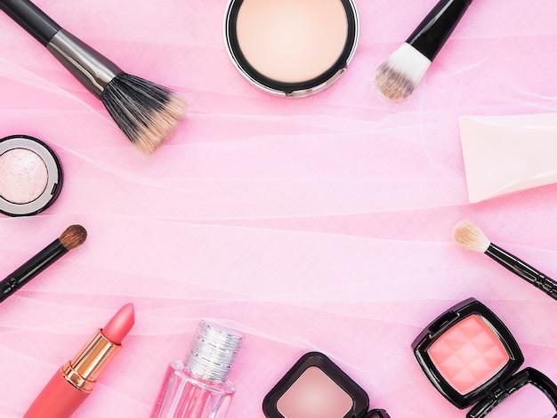 Lipstick, tools, eyeliner, blush, parfum, oogschaduw en poeder cosmetica in roze thema make-up op frame voor promotie.