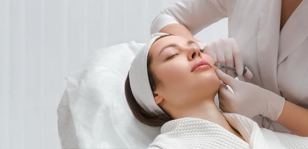 Lipvergroting en correctie procedure in een schoonheidssalon de specialist maakt een injectie