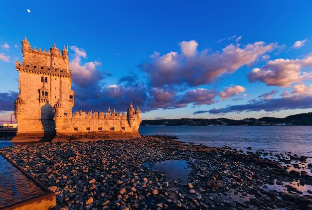 Lissabon, portugal - rotsachtige kust van een prachtige rivier waarop de belem-toren zich bevindt.