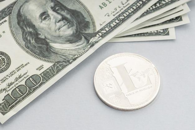 Litecoin-munt en een stapel amerikaanse dollarbankbiljetten. blockchain-geld versus fiat-geldconcept