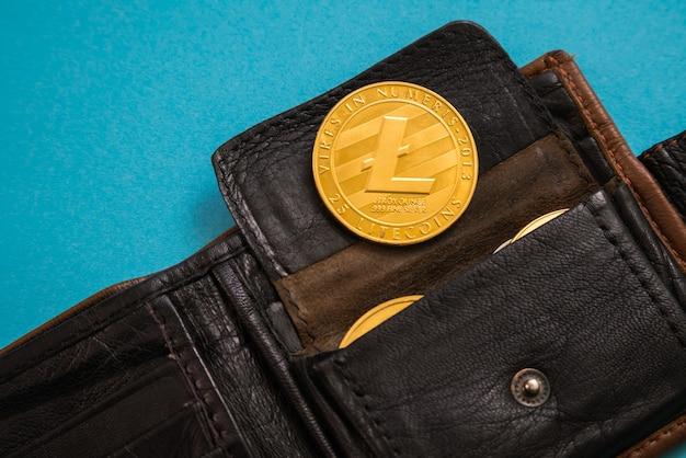 Litecoin steekt uit lederen portemonnee op blauwe achtergrond. digitale valuta