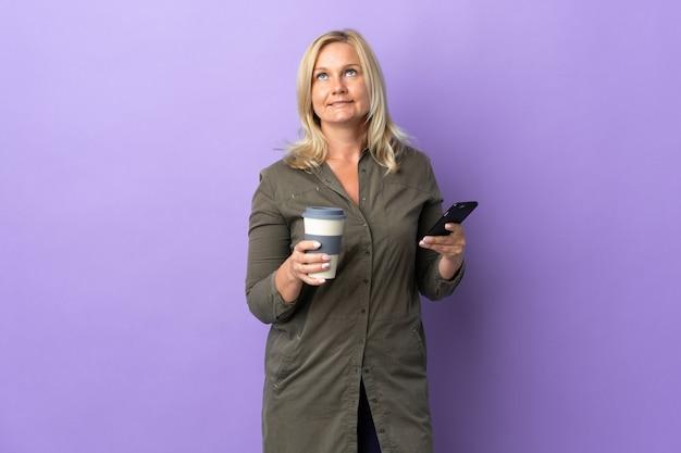 Litouwse vrouw van middelbare leeftijd geïsoleerd op paarse muur met koffie om mee te nemen en een mobiel terwijl ze iets denkt