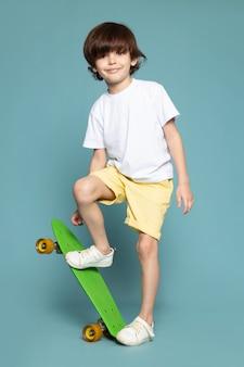 Litte jongen in wit t-shirt met skateboard op blauw