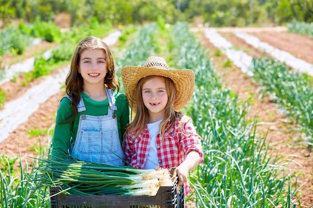 Litte kid boer meisjes in ui oogst boomgaard