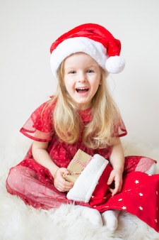Little beautiful girl in santa hat rode feestjurk wachten op kerstmis