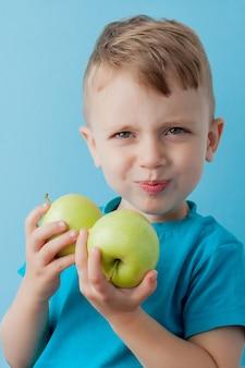 Little boy die appelen in zijn handen op blauwe achtergrond houden