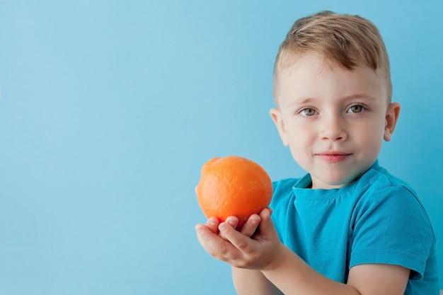 Little boy die een sinaasappel in zijn handen op blauw houden