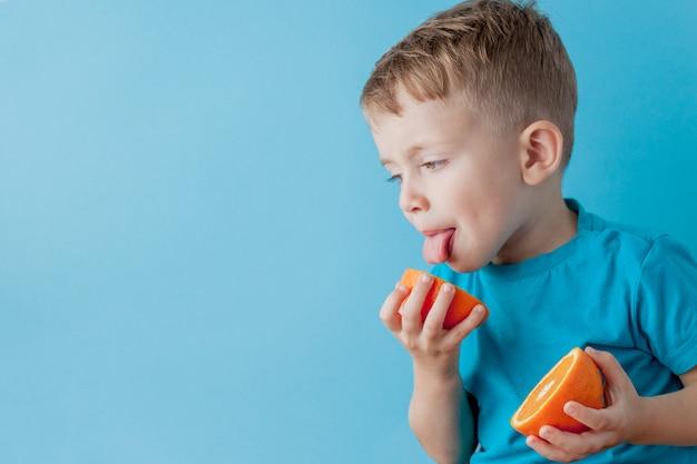 Little boy die een sinaasappel in zijn handen op blauwe achtergrond, dieet en oefening voor goed gezondheidsconcept houden